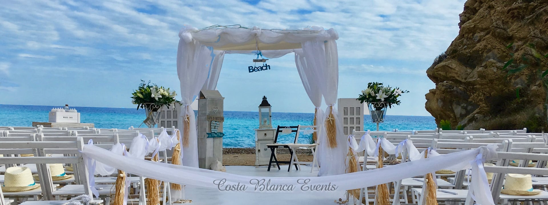 Photo of a ceremony setting with decorated gazebo and pew ends for a dream beach wedding in Spain