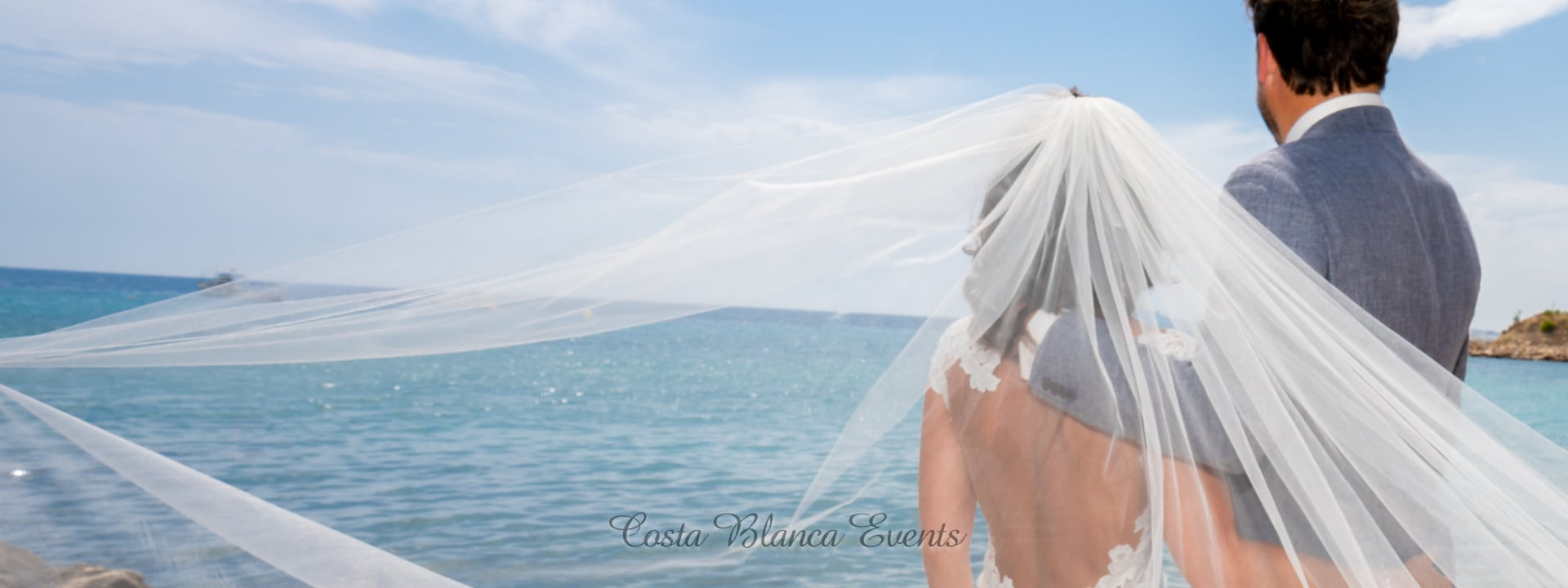 Photo of a bride and groom looking at the sea during a photoshoot on the wedding abroad